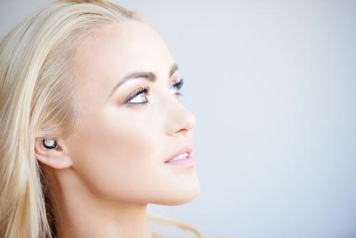 Nuheara Pretty blond woman daydreaming